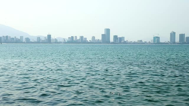 City on horizon with sea ripples on front of. video