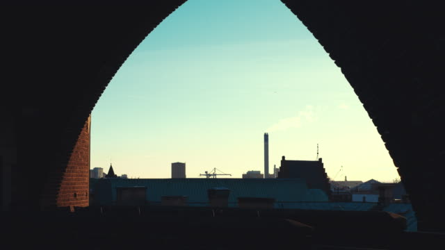 City view from brick wall window at dusk. Smokestack and silo, Helsingborg, Sweden video