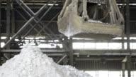Clamshell bucket crane pour white granular on mound video