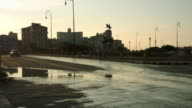 Classic car and motorcycle come to a stop on a wet street in Havana video
