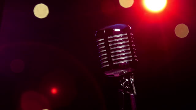 Classic microphone against dark blurry background with bright flashing lights video