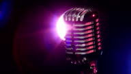 Classic microphone slow rotating on background lamp stroboscope in dark video