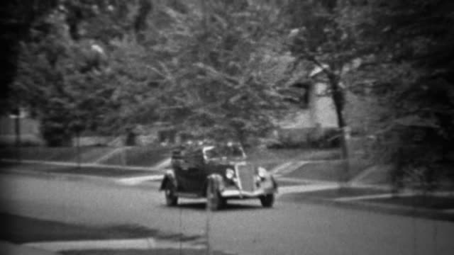 1935: Classic new black Plymouth car driving residential neighborhood. video