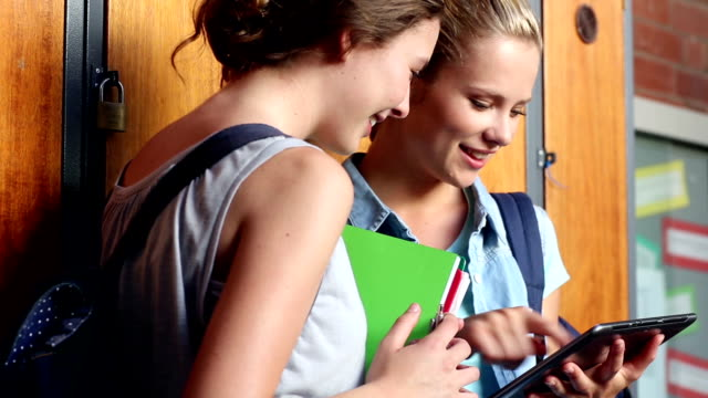 Classmates standing in hallway using tablet pc video