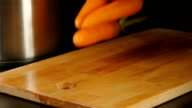 SLOW MOTION: Clean carrots fall on a cutting board on a kitchen video