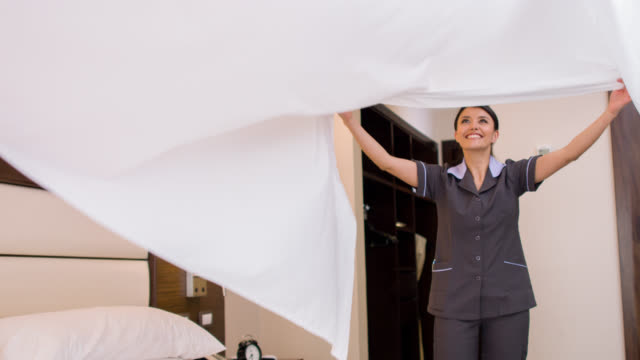 Cleaner working at a hotel making the bed video