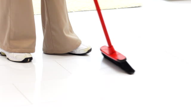 Cleaning woman sweeping floors with broom. video