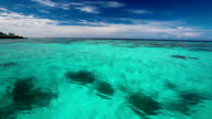 Clear blue lagoon with coral from moving boat, Maldives video