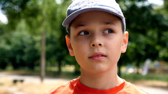 A clever boy in a cap thinks about his lefe standing in a park in slo-mo video