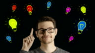 Clever creative man think gets an idea, which jumps up as symbolic colored cartoon animation shape lamps over his head on dark background video