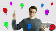 Clever hipster creative man think touch digital tablet ipad gets an idea, which jumps up as symbolic colored cartoon animation shape lamps around him on white background video