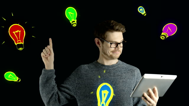 Clever hipster creative man think touch digital tablet ipad gets an idea, which jumps up as symbolic colored cartoon animation shape lamps around him on black background video