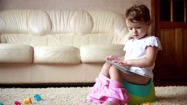 Clever toddler girl sitting on a potty and reading book. video