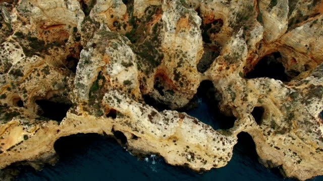 Cliffs in ocean near Ponte Piedade Lagos Portugal aerial view video