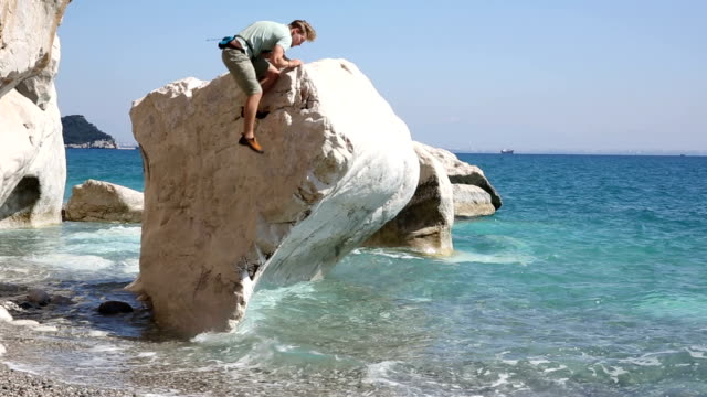 Climber ascends boulder in sea shallows video