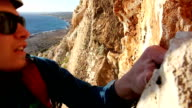 Climber ascends steep cliff above sea, adds pro video