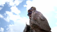 Climber ascends vertical pinnacle above mountains video