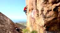 Climber belays teammate on steep cliff above sea video