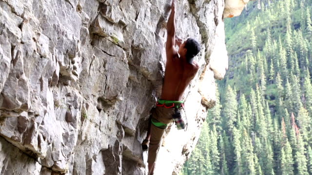 Climber belays teammate on steep cliff above valley video
