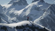 Climber exultant on a snow-covered mountain peak video