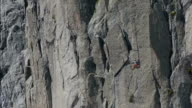 Climber making difficult move on high alpine wall video