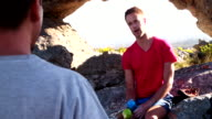 Climber Man talking to friends during rest from extreme rock climbing video