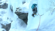 climber placing ice screw high up video