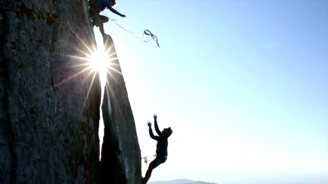 Climber throws rope to teammate, on cliff above hills, sea video