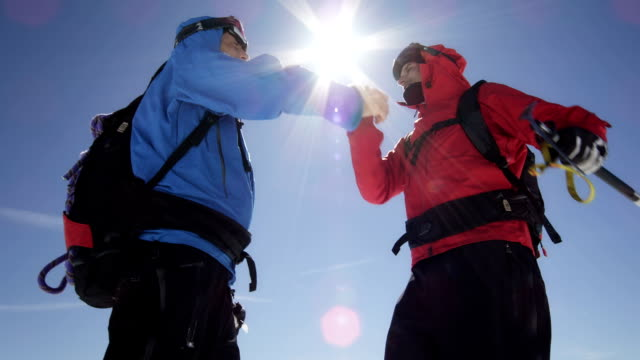 Climbers are shaking hands on a mountain peak video