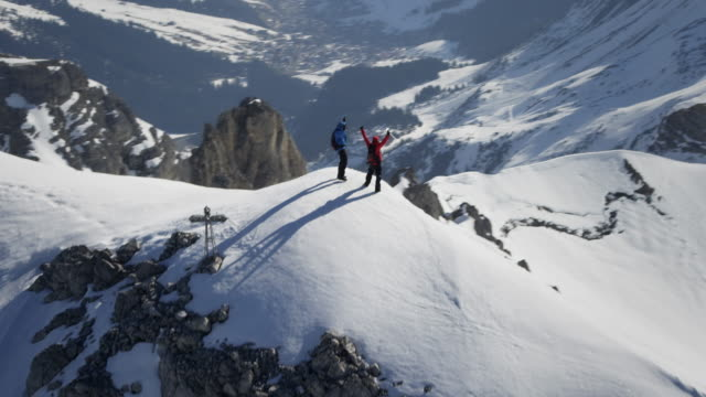 Climbers exultant on a snow-covered mountain peak with a cross on it video