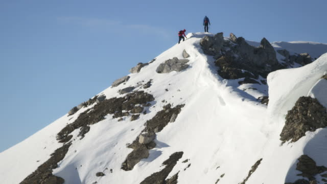 Climbers on the top of a snow-covered mountain video