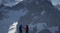 Climbers shaking hands on a snow-covered mountain peak video