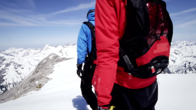 Climbers walk on a snow-covered mountain peak video