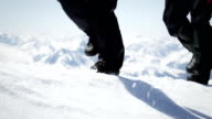Climbers walk over snow on a mountain video