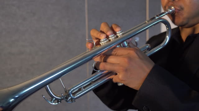 4K clip Footage of musician playing button and pushing on trumpet in Music room background.planing from right to left, Musical concept video
