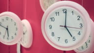 Clocks hanging on pink background video