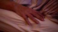 cloesup of old woman's hand lying in bed and a male hand is caressing her video