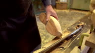 Clog maker cutting of the edges of a clog [Slomo] video
