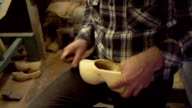 Clog maker is cutting decoration in clog with a gouge video