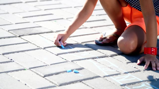 close up, a girl in sunglasses, draw drawings with colored crayons on the asphalt, street tiles. A hot summer day video