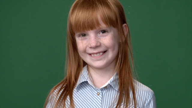 Close up bright ginger girl with freckles in a blue shirt smiling, chroma key green screen background video