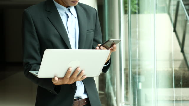 Close up Busy Businessman talking on Smartphone with Laptop in Office interior, Video Call On Mobile Phone video