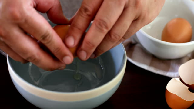Close up chef hand braking an egg into a blue bowl then mix to prepare omelet cooking , 4k Dci resolution video