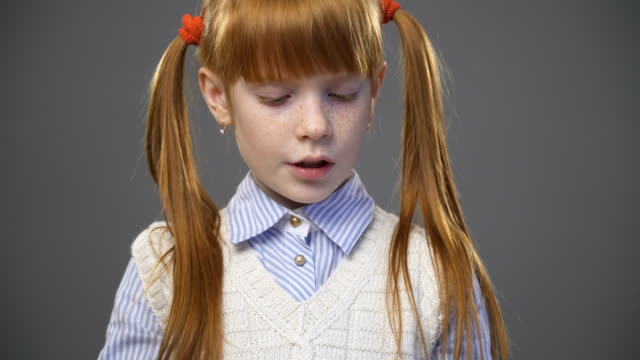 Close up cute ginger girl with pigtails is reading the book against gray background, pan video
