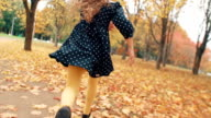 close up cute little girl with curly hair, in dress with polka dots runing through the autumn alley in the park slow mo video