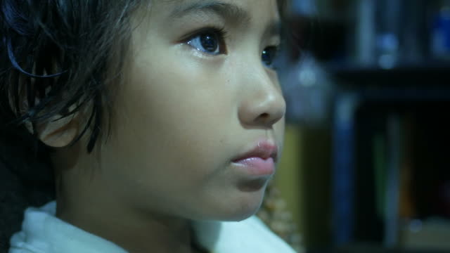close up face of Asian girl while looking at computer video