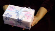 Close up, female hands giving a gift to boy video