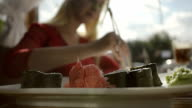 Close Up Girl eating Sushi with Chopsticks dipping in soy Sauce in a Restaurant video
