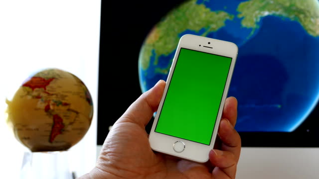 Close up hand holding green screen iphone and globe spinning on iMac video