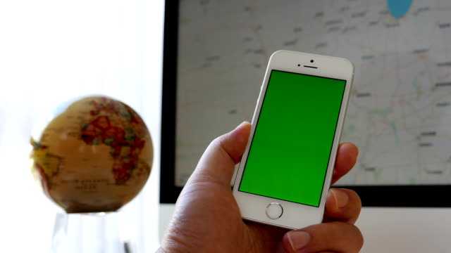 Close up hand holding green screen iphone and using google map on iMac video